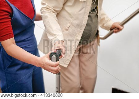 Elderly Asian Woman Using A Cane At Home With Daughter Take Care