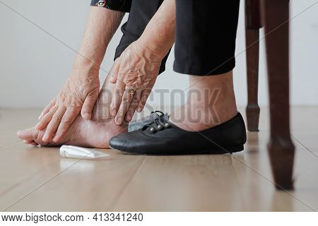 Elderly Woman Putting Cream On Swollen Feet Before Put On Shoes