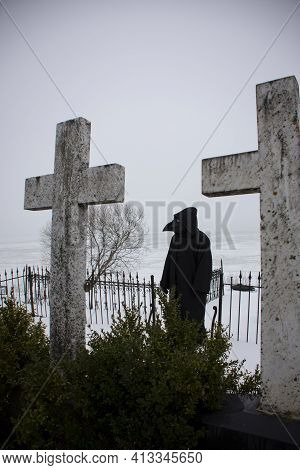 Medieval Plague Doctor Stands On Winter Graveyard Near Two Crosses, Corona Pandemic Symbol