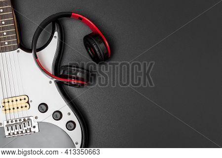 Electric Guitar With Headphones On Black Background.