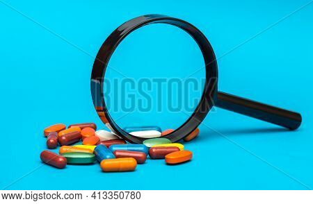 Magnifying Glass With Pills On A Blue.
