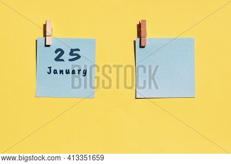 25 January. 25th Day Of The Month, Calendar Date. Two Blue Sheets For Writing On A Yellow Background