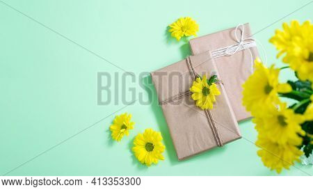 Handmade Gift Box Wrapped Craft Paper And Yellow Chrysanthemums On The Turquoise Background. Nice Gr
