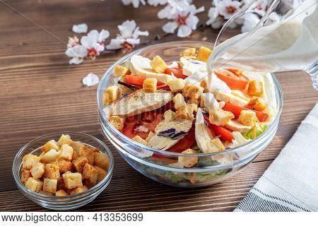 Sauce Caesar Pouring In Chicken Salad Caesar. Chicken Salad Caesar, Sauce And Croutons On The Wooden