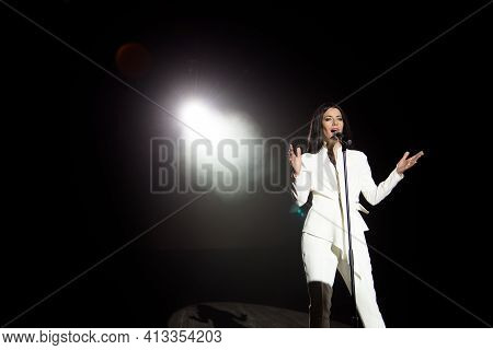 Singer Woman On Stage With Black Background In A Beam Of White Light.