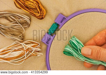 Preparation For Embroidery. Beige Cross Stitch Fabric In Plastic Embroidery Hoop, Three Color Flosse