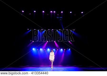Singer Star Performing Solo Set On Scene In Music Hall. Neon Background, Smoke, Concert Spotlights.
