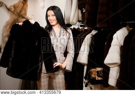 Woman With Fur Coat. Girl In A Fur Coat Coat In Shop With Fur On Background.