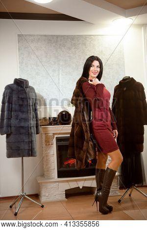 Beautiful Gir Posingl In Brown Fur Coat. Woman In Luxury Fur Coat At A Store.