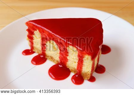 Plate Of A Slice Of Baked Cheesecake With Delectable Raspberry Sauce