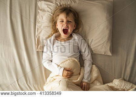 In The Early Morning, The Preschool Girl Lies In Bed And Yawns Violently, Her Mouth Is Open. Refuses
