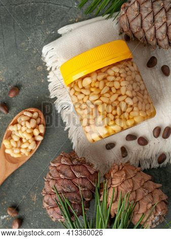 Pine Nut With Honey In A Transparent Jar. Yellow Cover. Next Is A Spoon With Honey And Pine Nuts. Co