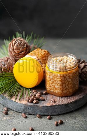 Pine Nuts With Honey In Transparent Jars. One Bank Is Open. Nearby Pine Nuts. Cones And Needles. Pla