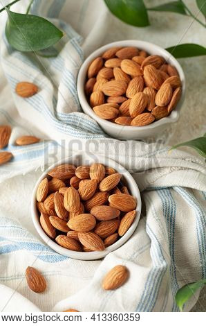 Almonds In Two White Cups. Fabric Background. Nearby Are Almonds And Green Leaves. View From Above.