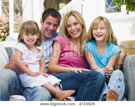 Families Sitting On Patio Smiling