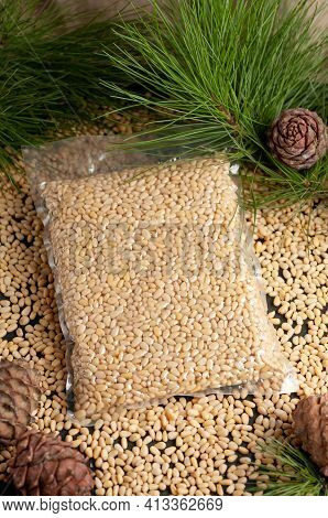 Peeled Pine Nut Kernel. Vacuum Packed. On A Wooden Background. Nearby Pine Nuts And Cones.