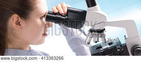 Doctor woman working  a microscope. Female scientist looking through a microscope in lab. Student girl looking in a microscope, science laboratory concept