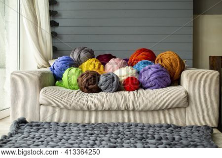 Bright Colorful Colored Balls Of Merino Wool On The Sofa Near The Window With A Gray Plaid On A Sunn