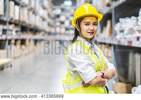 Portrait Of Asian Woman Warehouse Worker Are Posing And Smiling To The Camera In A Warehouse