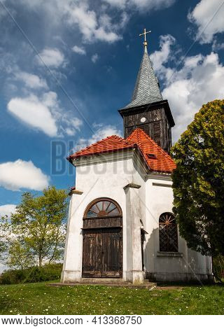 Old White Church With Wooden Door And Clock Tower
