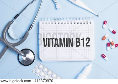 The Word Vitamin B12 Written On A White Notepad On A Blue Background Near A Stethoscope, Syringe, El
