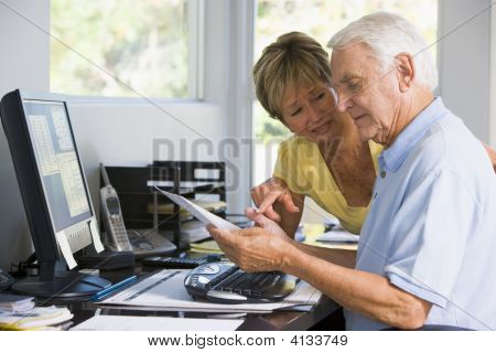 Couples In Home Office With Computer And Paperwork