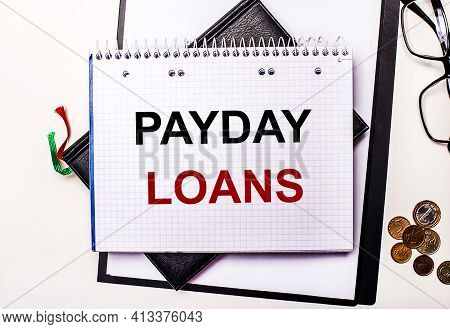 On A Light Background Glasses, Coins And A Notebook With The Inscription Payday Loans. Business Conc