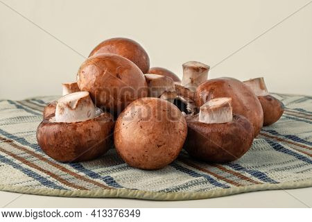 Champignon Mushrooms On A Towel. Brown Champignons On A Light Background. A Bunch Of Mushrooms. Natu
