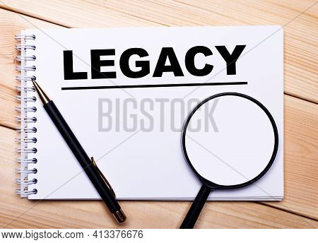 On A Light Wooden Background Lie A Pen, A Magnifying Glass And A Notebook With The Text Legacy