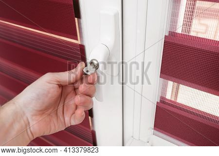 A Man Closes The Balcony Door On The Key. Close Up Photo. Child Safety At Home Concept - Door Lock O