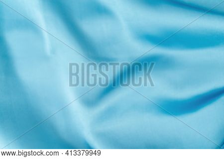 Blue Silk Fabric Defocused For Background. Abstract Blur Satin Fabric. Elegant Sky Color Background