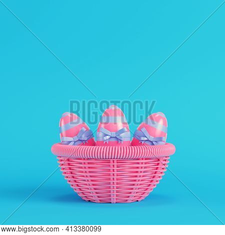 Pink Easter Eggs With Bow In A Wicker Basket On Bright Blue Background In Pastel Colors. Minimalism