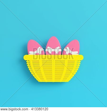 Yellow Easter Eggs With Bow In A Wicker Basket On Bright Blue Background In Pastel Colors. Minimalis