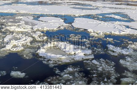 Thick White Snow-covered Ice Floes Float Along A Wide River Neman. Ice Drift. Winter In Europe