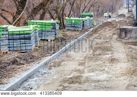 Paving Slabs In Stacks Are Located Along The Construction Site Of The City Park Walking Path. Laying