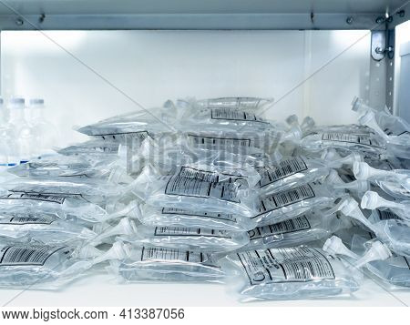 A Large Pile Of Intravenous Saline Bags In A Hospital On A Rack. The Inscription On The Package In R