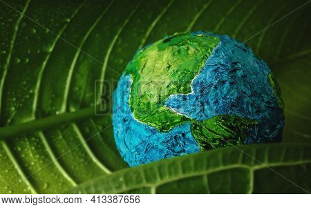 World Earth Day Concept. Green Moisture Leaf With Droplet Water Embracing A Handmade Globe. Environm
