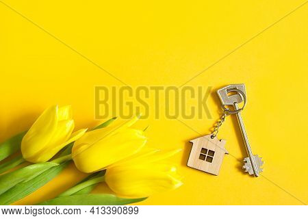 Key Ring In The Shape Of Wooden House With Key On Yellow Background And Spring Tulips. Building, Des