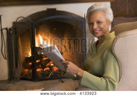 Woman Sitting In Living Room By Fireplace With Newspaper Smiling
