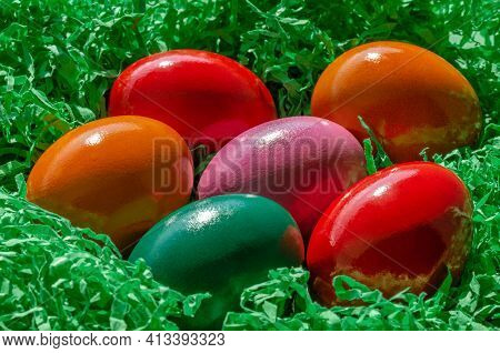 Easter Eggs Arranged In Green Paper Nest. Group Of Multicolored Paschal Eggs, Dyed Hard Boiled Chick