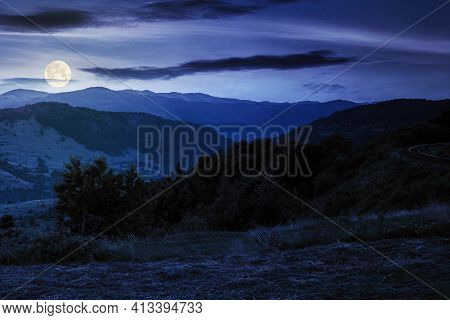Mountainous Rural Landscape At Night. Grassy Meadow On Top Of A Hill. Clouds Above The Ridge In Full