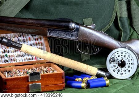 Shotgun With Cartridges And Fishing Rod With Fly Reel And Fly Box With Game Bag On Outdoor Coat