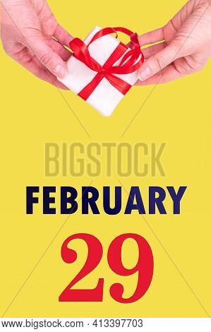 February 29th. Festive Vertical Calendar With Hands Holding White Gift Box With Red Ribbon And Calen