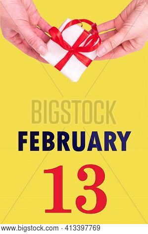 February 13th. Festive Vertical Calendar With Hands Holding White Gift Box With Red Ribbon And Calen