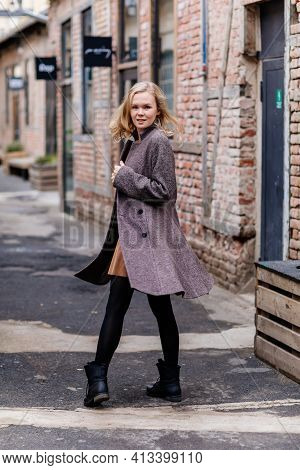 Girl In Black Tights, Beige Dress And Gray Coat, Beautiful Woman Has Fun In Vintage Street, Brick Wa