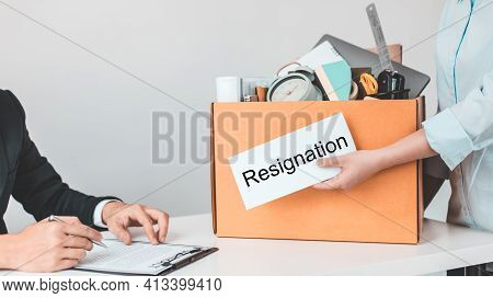 Employee handed over a document envelope and a box of work equipment beside him, Woman submits resig