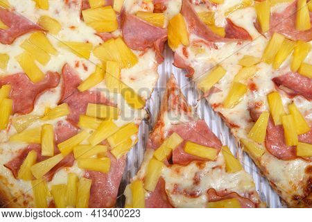 Top View Flat Lay Of One Whole Sliced Hawaiian Pizza In The Box. Covered With Canadian Bacon, Also K