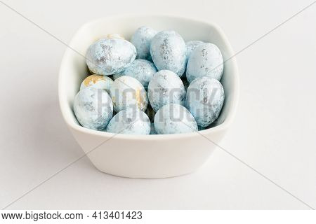 Blue Chocolate Coated Easter Eggs Candies On A Bowl Isolated On A White Table, Tasty Sugary Dessert