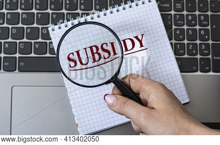 A Woman's Hand Holds A Magnifying Glass Over The Word Subsidy Against The Background Of A Laptop. Bu