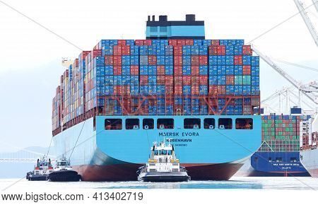 Oakland, Ca - Mar 10, 2021: Multiple Tugboats Assisting Cargo Ship Maersk Evora To Maneuver Into The